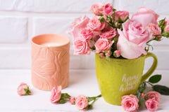 Ρόδινα λουλούδια τριαντάφυλλων στο πράσινο φλυτζάνι και το καίγοντας κερί ενάντια στο whi Στοκ Εικόνες