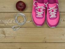 Ρόδινα πάνινα παπούτσια και η κόκκινη Apple σε ένα ξύλινο πάτωμα κορυφαία όψη Στοκ εικόνες με δικαίωμα ελεύθερης χρήσης