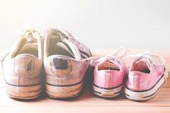 Ρόδινα πάνινα παπούτσια κοριτσιών και πάνινα παπούτσια λευκών σε ένα ξύλινο πάτωμα Στοκ εικόνα με δικαίωμα ελεύθερης χρήσης
