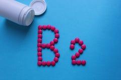 Ρόδινα στρογγυλά χάπια που ευθυγραμμίζονται με το γράμμα B2 στοκ εικόνες