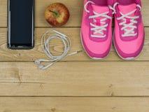 Ρόδινα τρέχοντας παπούτσια για τις κατηγορίες ικανότητας στη γυμναστική και η Apple στο ξύλινο πάτωμα επάνω από την όψη Στοκ Εικόνες