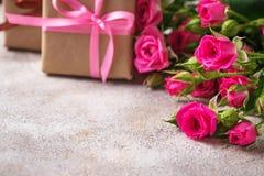 Ρόδινα τριαντάφυλλα και κιβώτια δώρων με τις κορδέλλες Στοκ Εικόνες