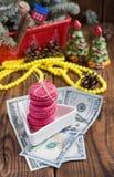 Ρόδινα macaroons και είκοσι δολάρια με τις διακοσμήσεις Χριστουγέννων στο ξύλινο υπόβαθρο Στοκ εικόνα με δικαίωμα ελεύθερης χρήσης