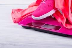 Ρόδινες πάνινα παπούτσια και μπλούζα, για την ικανότητα, στις ηλεκτρονικές κλίμακες, σε ένα γκρίζο υπόβαθρο στοκ εικόνες