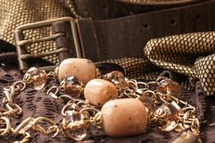 Ρόδινες χάντρες, χρυσές αλυσίδα και ζώνη δέρματος στην καφετιά δαντέλλα στοκ φωτογραφίες με δικαίωμα ελεύθερης χρήσης