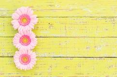 Ρόδινη διακόσμηση συνόρων λουλουδιών στο shabby κίτρινο ξύλινο υπόβαθρο Στοκ Εικόνα