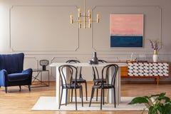 Ρόδινη και μπλε ναυτική αφηρημένη ζωγραφική σε έναν γκρίζο τοίχο με τη σχηματοποίηση κομψά να δειπνήσει και ένα καθιστικό στοκ φωτογραφία