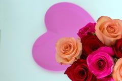 Ρόδινη καρδιά στο κέντρο με τα ρόδινα και κόκκινα τριαντάφυλλα στη δεξιά γωνία στοκ εικόνες