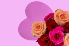 Ρόδινη καρδιά στο κέντρο με τα ρόδινα και κόκκινα τριαντάφυλλα στη δεξιά γωνία στοκ φωτογραφία