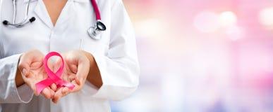 Ρόδινη κορδέλλα συνειδητοποίησης καρκίνου εκμετάλλευσης χεριών γιατρών στοκ εικόνα