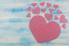 Ρόδινη λαμπρή καρδιά σε ένα μπλε ξύλινο υπόβαθρο επάνω από την όψη τοποθετήστε το κείμενο βαλεντίνος ημέρας s στοκ φωτογραφίες