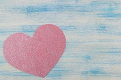Ρόδινη λαμπρή καρδιά σε ένα μπλε ξύλινο υπόβαθρο επάνω από την όψη τοποθετήστε το κείμενο βαλεντίνος ημέρας s στοκ εικόνες με δικαίωμα ελεύθερης χρήσης