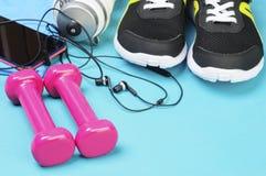 Ρόδινοι αλτήρες, αθλητικό μπουκάλι, ακουστικά και τρέχοντας παπούτσια στο αθλητικό χαλί Στοκ Φωτογραφίες