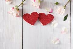 Ρόδινος αυξήθηκε πέταλα λουλουδιών και χειροποίητος ξύλινος ακτινοβολεί καρδιές στο άσπρο αγροτικό ξύλο Στοκ Εικόνες
