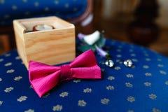 Ρόδινος δεσμός τόξων, όμορφα μανικετόκουμπα γυαλιού, μπουτονιέρα λουλουδιών Ένα σύνολο των ατόμων εξαρτημάτων σε μια παλαιά ξύλιν στοκ εικόνες
