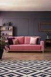 Ρόδινος καναπές βελούδου με τα μαξιλάρια που στέκονται στη μέση του σκοτεινού γ Στοκ εικόνα με δικαίωμα ελεύθερης χρήσης