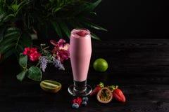 Ρόδινος καταφερτζής σε ένα ψηλό γυαλί και φρούτα σε ένα σκοτεινό υπόβαθρο στοκ εικόνα