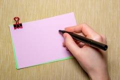 ρόδινο έγγραφο με το χέρι paperclip και γυναικών που κρατά μια μάνδρα περίπου που γράφει Αντικείμενα που απομονώνονται σε κίτρινο Στοκ Φωτογραφίες
