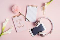 Ρόδινο ακουστικό, τηλέφωνο, κενές σημειωματάριο και μάνδρα στο ρόδινο υπόβαθρο με τα λουλούδια, τοπ άποψη στοκ εικόνα
