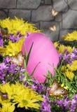 Ρόδινο αυγό Πάσχας στα λουλούδια Στοκ εικόνες με δικαίωμα ελεύθερης χρήσης