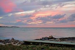 Ρόδινο ηλιοβασίλεμα από το φραγμό και τα κάγκελα Lenny στους κοκοφοίνικες Cayo, Κούβα στοκ εικόνες