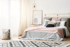 Ρόδινο κάλυμμα στο γκρίζο κρεβάτι στο σύγχρονο εσωτερικό κρεβατοκάμαρων με την αφίσα στοκ εικόνα