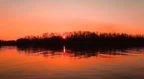 Ρόδινο και πορτοκαλί ηλιοβασίλεμα πέρα από τον ποταμό Στοκ Φωτογραφία