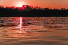 Ρόδινο και πορτοκαλί ηλιοβασίλεμα πέρα από τον ποταμό Στοκ Εικόνα