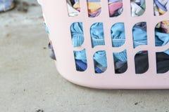 Ρόδινο καλάθι με το βρώμικο πλυντήριο στο πάτωμα στοκ φωτογραφία με δικαίωμα ελεύθερης χρήσης