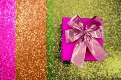 Ρόδινο κιβώτιο δώρων με ένα τόξο σε ένα λαμπιρίζοντας υπόβαθρο χρώματος στοκ εικόνες