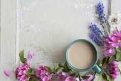 Ρόδινο πλαίσιο λουλουδιών άνοιξη τέχνης με το φλυτζάνι στο παλαιό άσπρο ξύλινο υπόβαθρο Στοκ φωτογραφίες με δικαίωμα ελεύθερης χρήσης