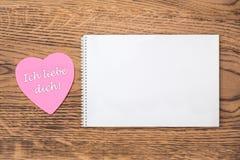"""Ρόδινο post-it καρδιών με το κείμενο """"Ich liebe dich """"και ένα σημειωματάριο σε ένα ξύλινο υπόβαθρο Μετάφραση: """"Σ' αγαπώ """" στοκ εικόνα με δικαίωμα ελεύθερης χρήσης"""