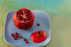 Ρόδι και κόκκινοι σπόροι των φρούτων σε ένα μπλε πιάτο Όμορφα φωτεινά τροπικά φρούτα στοκ εικόνα με δικαίωμα ελεύθερης χρήσης