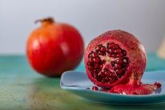 Ρόδι και κόκκινοι σπόροι των φρούτων σε ένα μπλε πιάτο Όμορφα φωτεινά τροπικά φρούτα σε έναν πράσινο πίνακα στοκ φωτογραφίες