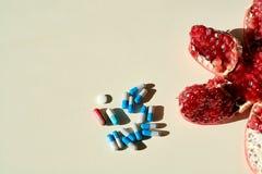 Ρόδι, ταμπλέτες και κάψες, χάπια Έννοια μιας υγιούς ζωής στοκ φωτογραφίες