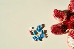 Ρόδι, ταμπλέτες και κάψες, χάπια Έννοια μιας υγιούς ζωής στοκ φωτογραφία με δικαίωμα ελεύθερης χρήσης