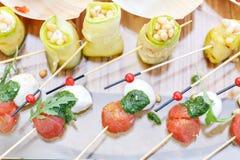Ρόλοι κολοκυθιών με τα καρύδια πεύκων Ντομάτες, μοτσαρέλα και βασιλικός κερασιών στα οβελίδια Σάλτσα Pesto Νόστιμος πίνακας μπουφ στοκ εικόνα