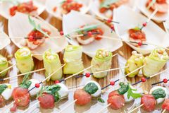 Ρόλοι κολοκυθιών με τα καρύδια πεύκων Ντομάτες, μοτσαρέλα και βασιλικός κερασιών στα οβελίδια Σάλτσα Pesto Νόστιμος πίνακας μπουφ στοκ φωτογραφία