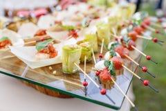 Ρόλοι κολοκυθιών με τα καρύδια πεύκων Ντομάτες, μοτσαρέλα και βασιλικός κερασιών στα οβελίδια Σάλτσα Pesto Νόστιμος πίνακας μπουφ στοκ εικόνες