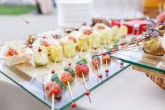 Ρόλοι κολοκυθιών με τα καρύδια πεύκων Ντομάτες, μοτσαρέλα και βασιλικός κερασιών στα οβελίδια Σάλτσα Pesto Νόστιμος πίνακας μπουφ στοκ φωτογραφία με δικαίωμα ελεύθερης χρήσης