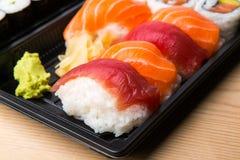 Ρόλοι σουσιών και Sashimi σε έναν ξύλινο πίνακα Φρέσκα γίνοντα σούσια που τίθενται με το σολομό, τις γαρίδες, το wasabi και την π Στοκ Εικόνες