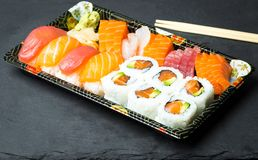 Ρόλοι σουσιών και Sashimi σε μια μαύρη πέτρα slatter Φρέσκα γίνοντα σούσια που τίθενται με το σολομό, τις γαρίδες, το wasabi και  Στοκ εικόνα με δικαίωμα ελεύθερης χρήσης