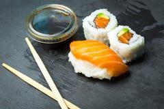 Ρόλοι σουσιών και Sashimi σε μια μαύρη πέτρα slatter Φρέσκα γίνοντα σούσια που τίθενται με το σολομό, τις γαρίδες, το wasabi και  Στοκ Φωτογραφίες