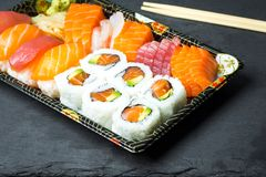 Ρόλοι σουσιών και Sashimi σε μια μαύρη πέτρα slatter Φρέσκα γίνοντα σούσια που τίθενται με το σολομό, τις γαρίδες, το wasabi και  Στοκ φωτογραφία με δικαίωμα ελεύθερης χρήσης