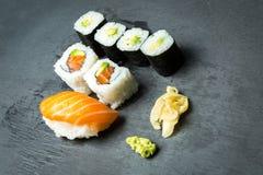 Ρόλοι σουσιών και Sashimi σε μια μαύρη πέτρα slatter Φρέσκα γίνοντα σούσια που τίθενται με το σολομό, τις γαρίδες, το wasabi και  Στοκ φωτογραφίες με δικαίωμα ελεύθερης χρήσης