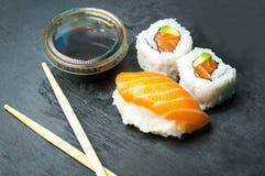 Ρόλοι σουσιών και Sashimi σε μια μαύρη πέτρα slatter Φρέσκα γίνοντα σούσια που τίθενται με το σολομό, τις γαρίδες, το wasabi και  Στοκ Εικόνες
