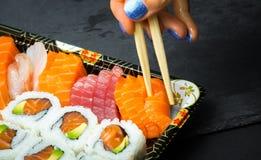 Ρόλοι σουσιών και Sashimi σε μια μαύρη πέτρα slatter Φρέσκα γίνοντα σούσια που τίθενται με το σολομό, τις γαρίδες, το wasabi και  Στοκ Φωτογραφία