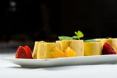 Ρόλοι των λεπτών τηγανιτών με τον καπνισμένο σολομό, το τυρί κρέμας χρένου και τα φύλλα πυραύλων στο άσπρο πιάτο στο μαύρο υπόβαθ Στοκ Φωτογραφία