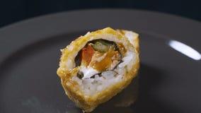 Ρόλος σουσιών που περιστρέφεται στο μαύρο υπόβαθρο Ιαπωνικά τρόφιμα σουσιών στο εστιατόριο Ρόλος σουσιών Καλιφόρνιας που τίθεται  φιλμ μικρού μήκους