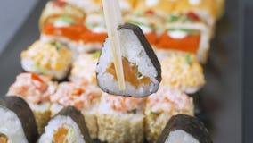 Ρόλος σουσιών που περιστρέφεται στο μαύρο υπόβαθρο Ιαπωνικά τρόφιμα σουσιών στο εστιατόριο Επιλογές εστιατορίων της Ιαπωνίας 4K β απόθεμα βίντεο